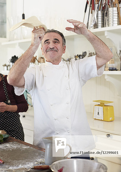 Playful senior chef tossing pizza dough in kitchen