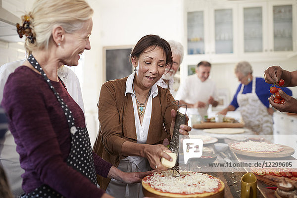 Senior women friends grating cheese over pizza in cooking class