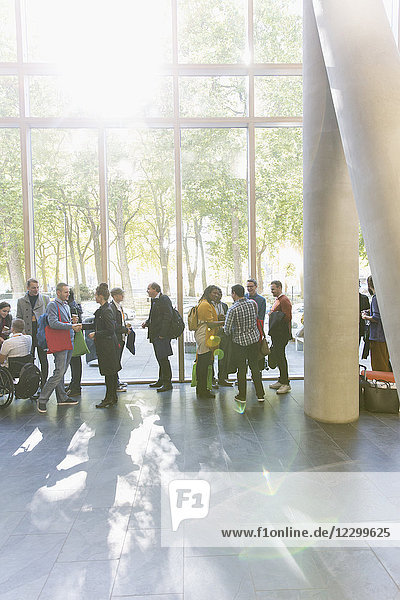 Business people networking at conference  talking in sunny lobby