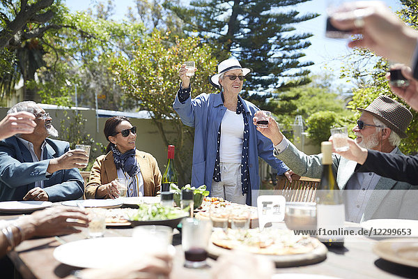 Happy senior woman toasting wine with friends at sunny garden party