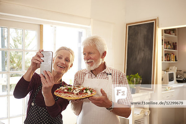 Smiling  confident senior couple taking selfie with pizza at cooking class