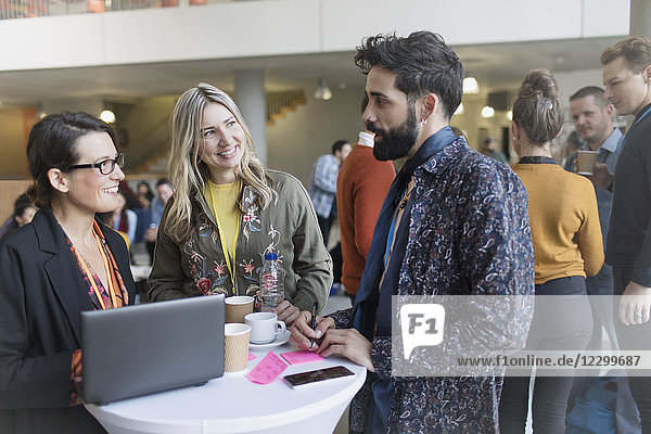 Business people talking  using laptop at conference