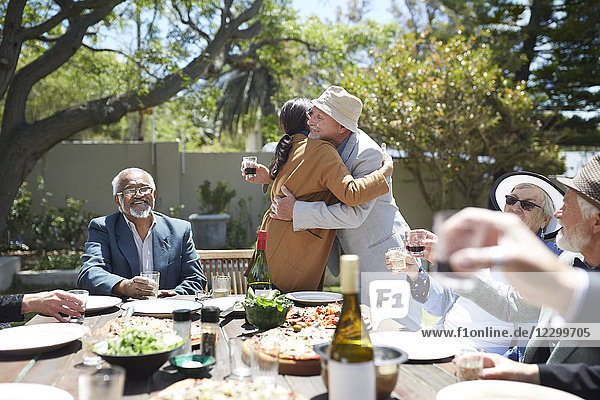Friends toasting affectionate senior couple hugging at sunny garden party