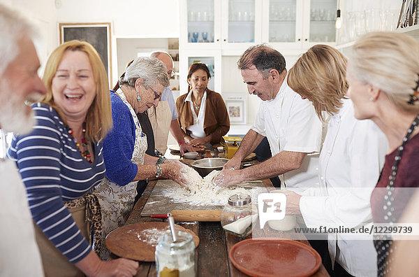 Senior friends enjoying pizza cooking class  making dough