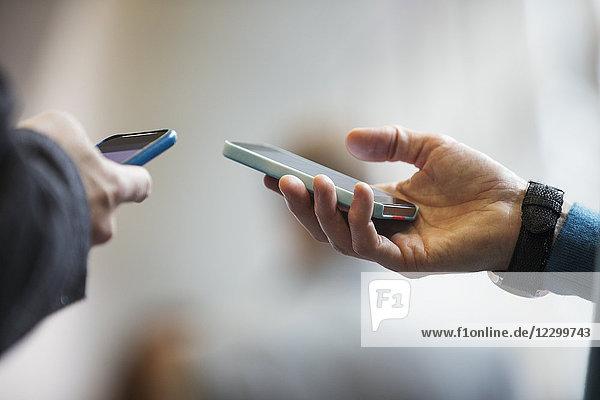 Close up men holding smart phones