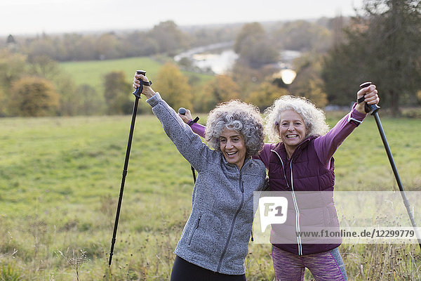 Portrait confident  enthusiastic active senior women friends hiking with poles in rural field