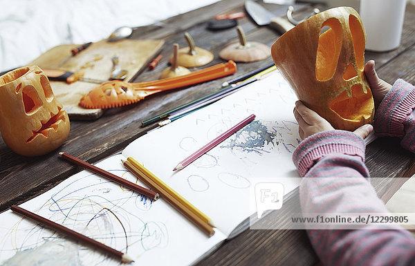 Creative girl carving Halloween pumpkins