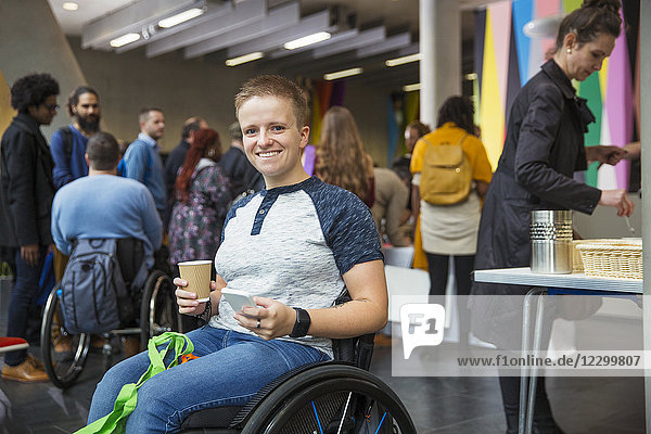 Portrait smiling  confident woman in wheelchair using smart phone at conference