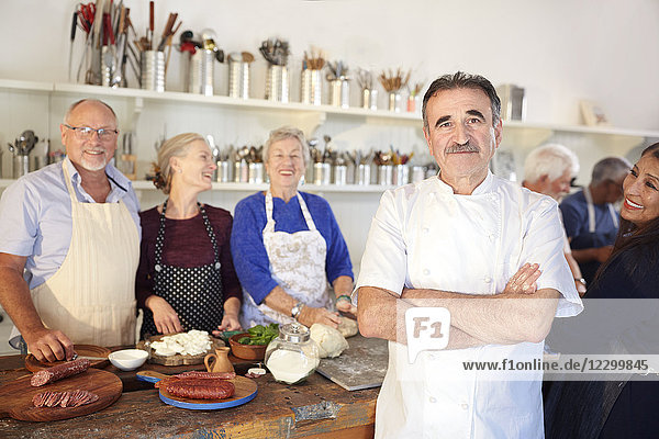 Portrait confident chef with senior students in cooking class kitchen