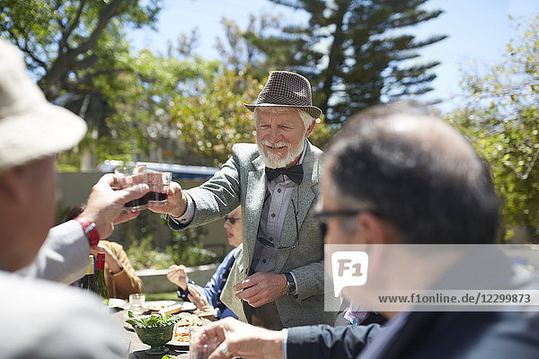 Senior man in suit and bow tie toasting friends with wine at sunny garden party