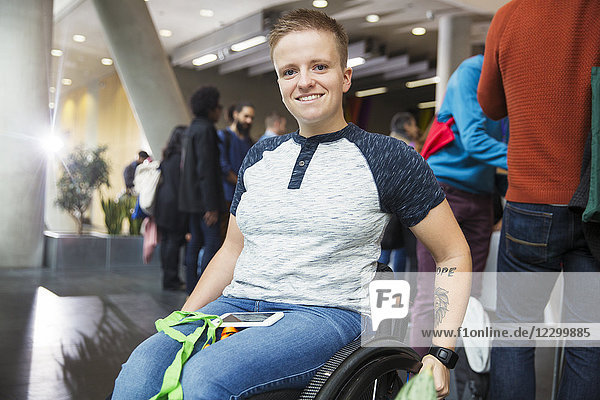 Portrait smiling young woman in wheelchair at conference