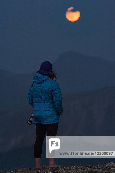 Female photographer looking at view of Full Moon  Aspen  Colorado  USA