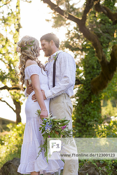 Bride and groom on the edge of a cliff overlooking the beautiful North Umpqua River near Glide Oregon during a romantic elopement style wedding.