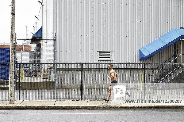 Shirtless man jogging on pavement along fence of industrial building  Boston  Massachusetts  USA