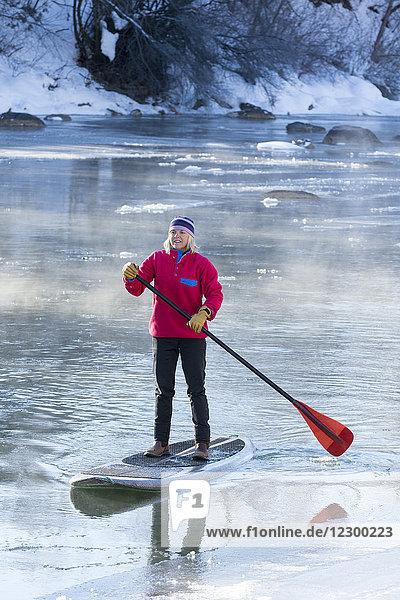 Adult woman paddleboarding across icy Animas River during winter  Durango  Colorado  USA