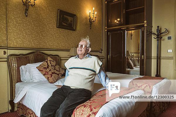 Portrait of senior man sitting on hotel bed with smile  Alexandria  Egypt