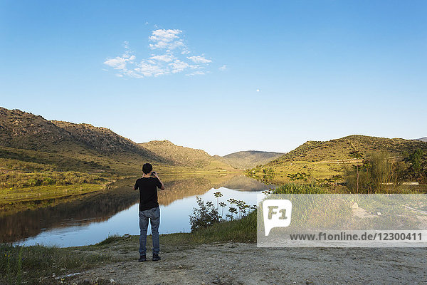 Teenager photographing River Douro and surrounding landscape with smart phone  Portugal