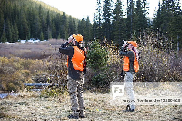 Two hunters searching for animals with binoculars  Colorado  USA