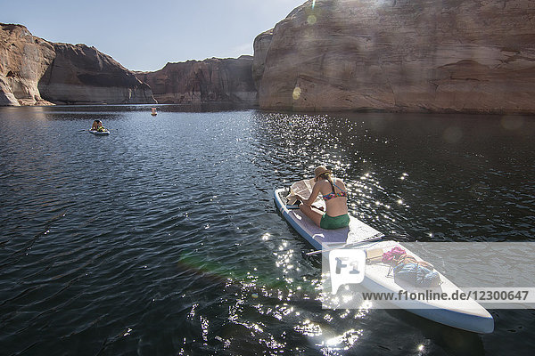 Rear view of woman looking at map while sitting on stand-up paddleboard  Lake Powell  Utah  USA