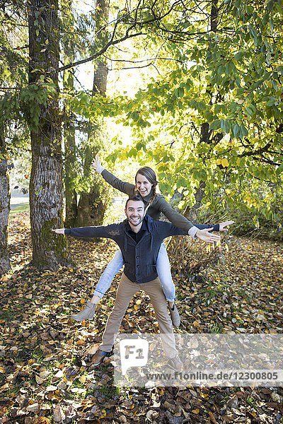 Front view portrait of couple with arms outstretched in park