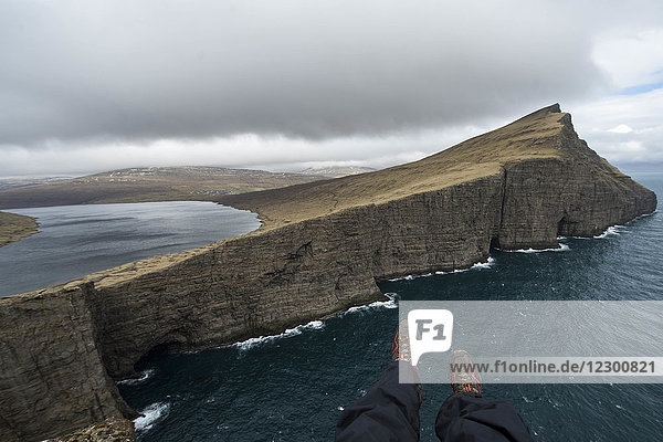 Hikers feet sticking over edge of sea cliff  Faroe Islands