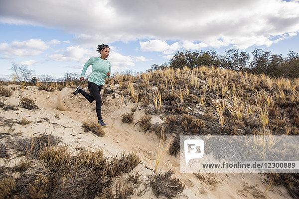 Young woman running down sandy hill during sunny weather,  Newburyport,  Massachusetts,  USA