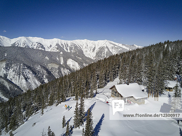 Aerial view of skiing couple descending from isolated cabin on top of snowcapped mountain  Aspen  Colorado  USA