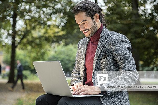 Man with beard and in blazer using laptop while sitting in park
