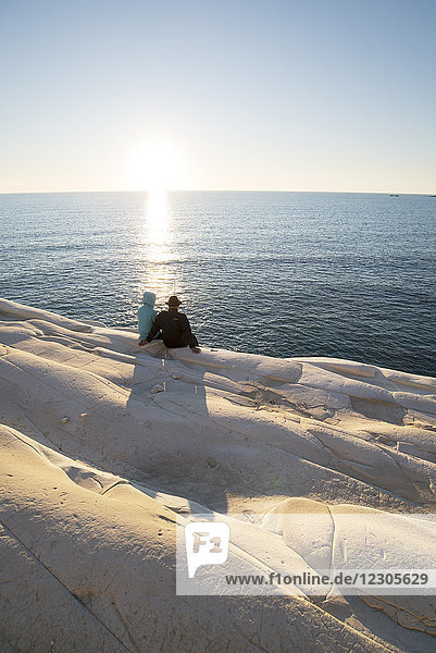 Rear view of couple looking at sea while sitting at Scala dei Turchi cliff  Sicily  Italy