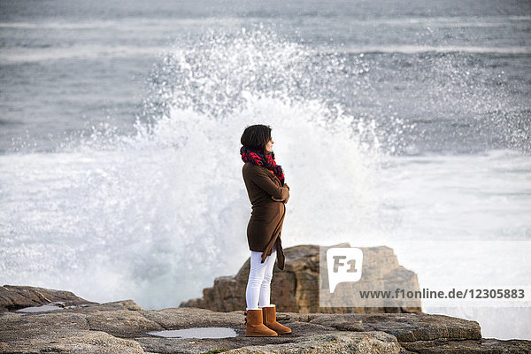 Side view of woman standing on rocky coastline with waves crashing behind
