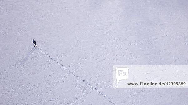 Aerial view of lone man walking on frozen lake in winter