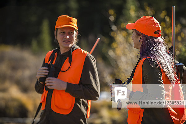 Male and female hunters talking outdoors with binoculars in hands  Colorado  USA