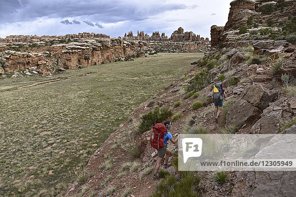 Two female backpackers on trail overlooking The Needles in Canyonlands National Park  Moab  Utah  USA