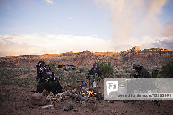 Group of three men and one woman sitting around campfire in Moab  Utah  USA