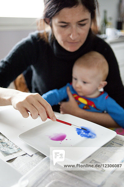 Mother helping baby paint art dripping paint on paper  Kerroch  Brittany  France