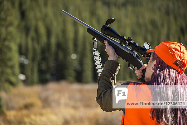 Rear view of female hunter with dyed hair aiming hunting rifle  Colorado  USA