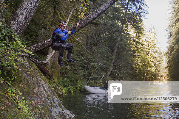 Side view of man on rope swing on riverbank in forest  Opal Creek Wilderness  Oregon  USA