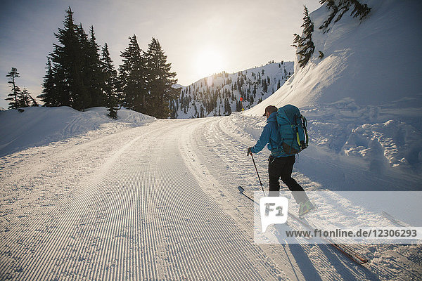 Rear view of man cross-country skiing down snowy road  North Cascades National Park  Washington State  USA