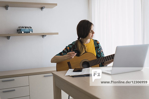 Young woman sitting at table at home with laptop playing guitar