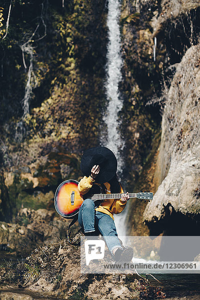 Spanien  Lleida  junge Frau mit Gitarre auf dem Felsen vor dem Wasserfall sitzend  Gesicht mit Hut bedeckend