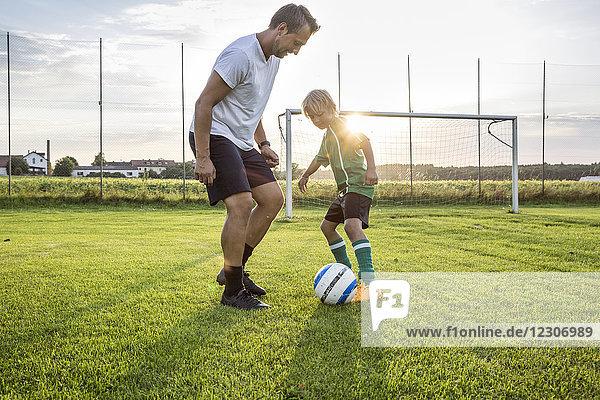 Trainer und junger Fußballspieler auf dem Fußballplatz bei Sonnenuntergang