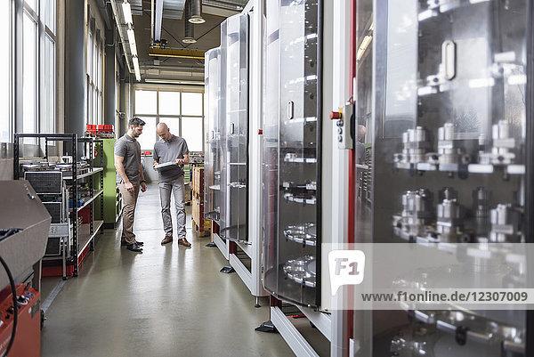 Zwei Männer untersuchen das Produkt in einer modernen Fabrik