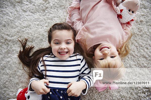 Porträt von zwei grinsenden kleinen Schwestern  die auf dem Teppich liegen.