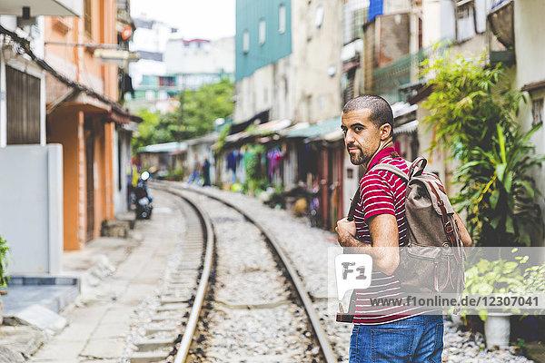 Vietnam  Hanoi  Mann in der Stadt mit Eisenbahnschienen entlang der Häuser