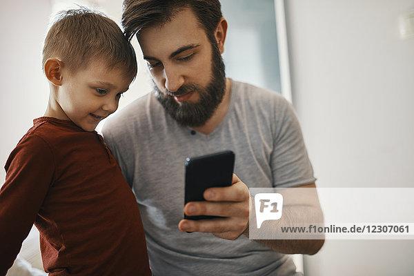 Vater erklärt kleinen Sohn Smartphone