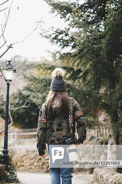 Rückansicht des jungen Fotografen im Freien