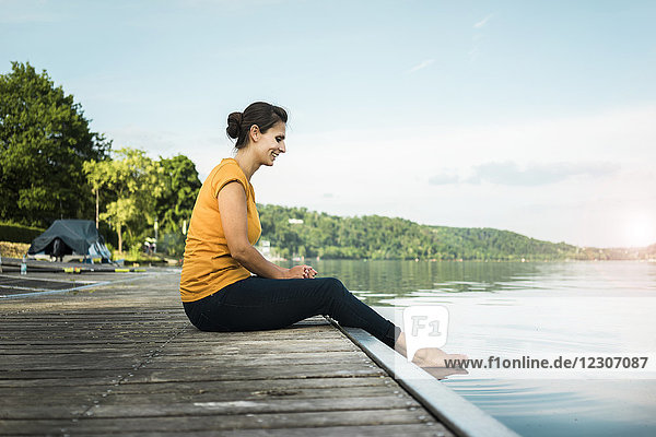 Happy woman sitting on jetty at a lake