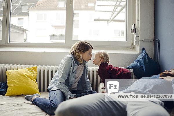Familie entspannt zu Hause auf dem Sofa  Mutter küsst Baby-Sohn