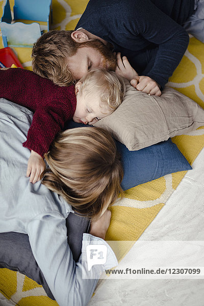 Gestaffelte Familie  die nach dem Spielen zusammen auf dem Boden ruht.
