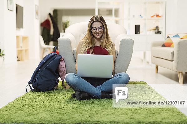Lässige junge Frau mit Laptop im Coworking Space